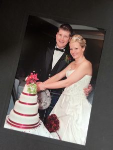 A happy couple cut into their beautiful home made wedding cake on their wedding day